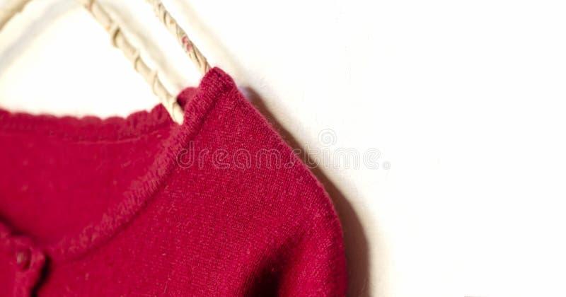 Una rebeca en la ejecución roja en la suspensión de ropa en el fondo blanco foto de archivo libre de regalías
