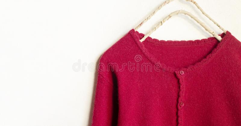 Una rebeca en la ejecuci?n roja en la suspensi?n de ropa en el fondo blanco imagen de archivo libre de regalías