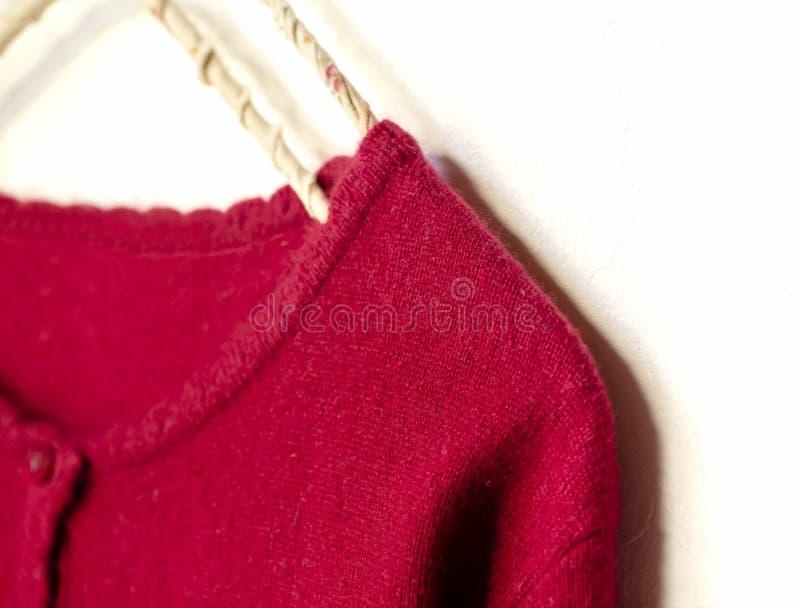 Una rebeca en la ejecuci?n roja en la suspensi?n de ropa en el fondo blanco fotos de archivo