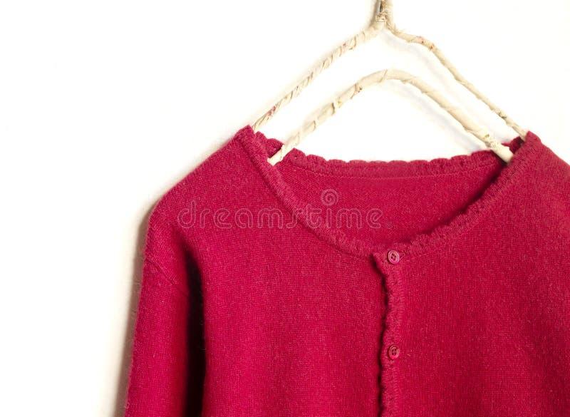 Una rebeca en la ejecuci?n roja en la suspensi?n de ropa en el fondo blanco fotografía de archivo