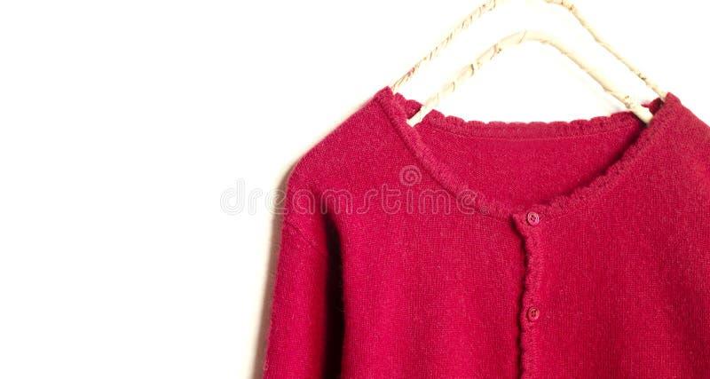 Una rebeca en la ejecuci?n roja en la suspensi?n de ropa en el fondo blanco imágenes de archivo libres de regalías