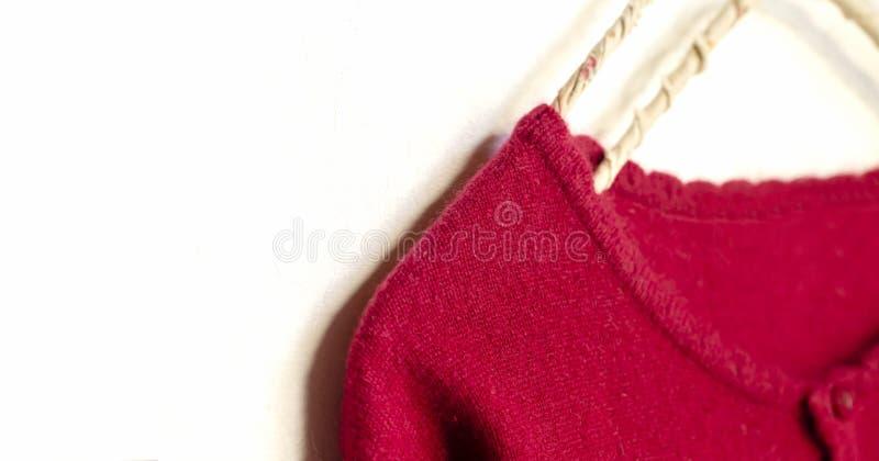Una rebeca en la ejecuci?n roja en la suspensi?n de ropa en el fondo blanco foto de archivo