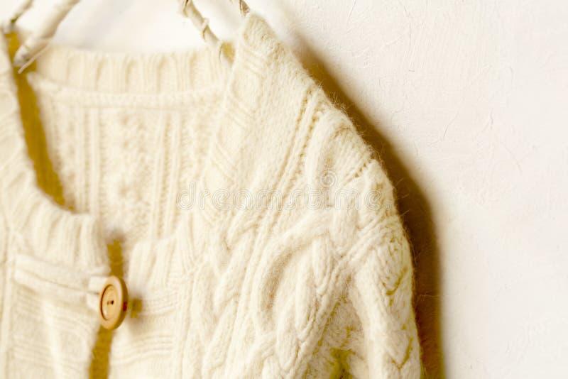 Una rebeca hecha punto gruesa en la ejecución blanca en la suspensión de ropa en el fondo blanco imagenes de archivo