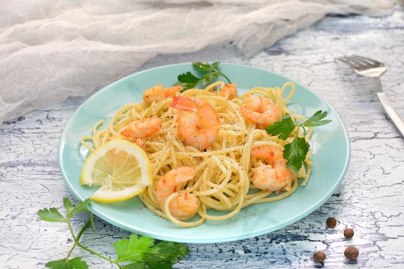 Una receta deliciosa de los espaguetis con el camarón y la pimienta, adornados con el limón y un grano de pimienta Cena agradable foto de archivo libre de regalías