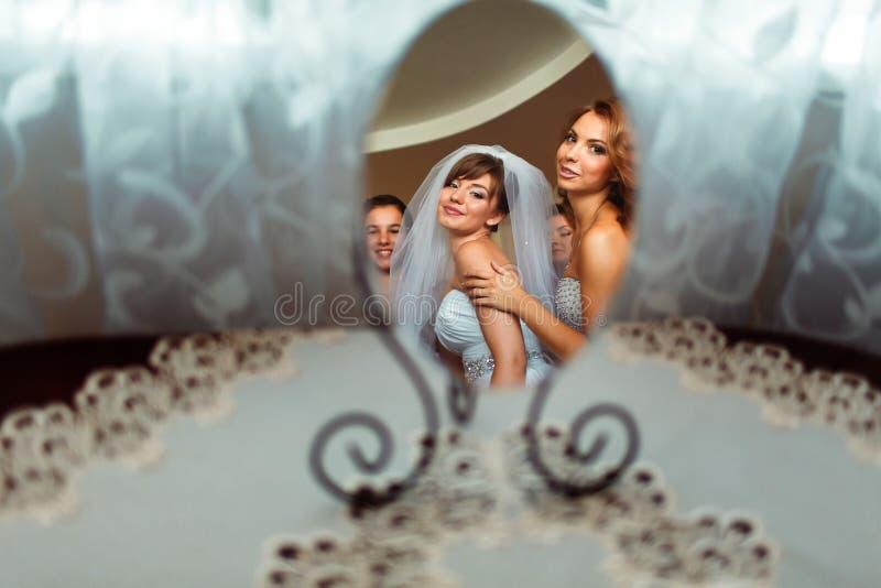 Una reflexión de una novia y de damas de honor en un pequeño espejo redondo imagenes de archivo