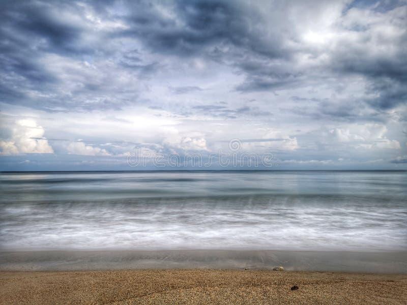 Una reflexi?n lisa sedosa chapoteante hermosa del agua que salpica en la playa imágenes de archivo libres de regalías
