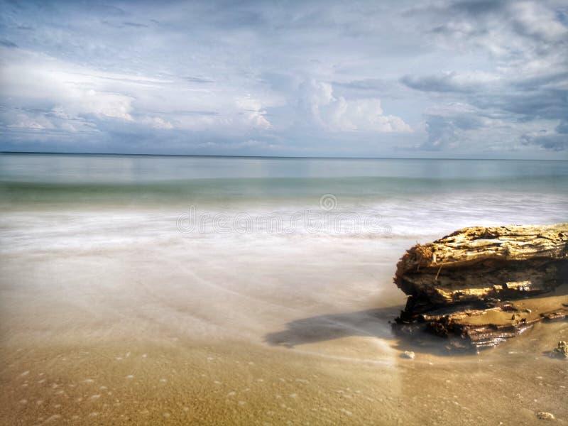Una reflexi?n lisa sedosa chapoteante hermosa del agua que salpica en la playa fotografía de archivo
