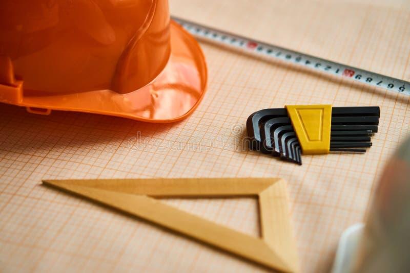Una regla triangular, un edificio de la ruleta, un casco anaranjado, dibujos fotos de archivo libres de regalías