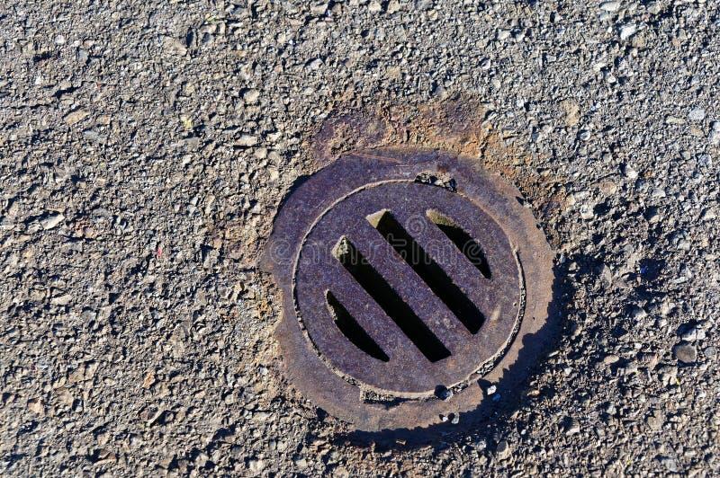 Una rejilla redonda, oxidada del metal sobre un dren de la precipitación excesiva fotografía de archivo