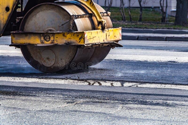 Una reparación del camino y un rodillo amarillo oxidado viejo desarrolla una capa delgada de un nuevo negro fuming el asfalto cal fotografía de archivo