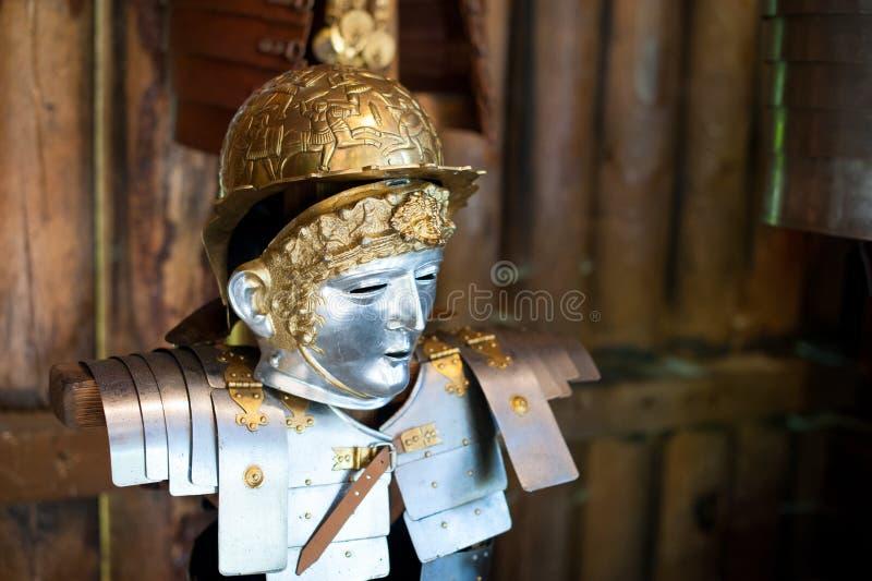Una reproducción de un casco cuaternario romano antiguo contra una pared de madera del registro imagen de archivo libre de regalías
