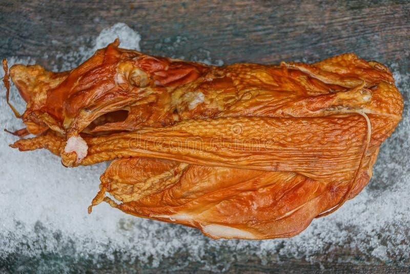 Una res muerta entera del pollo frito marrón en la nieve blanca en una tabla gris fotos de archivo libres de regalías