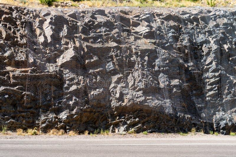Una rete disposta sopra le rocce lungo il lato di una strada della montagna fotografia stock libera da diritti