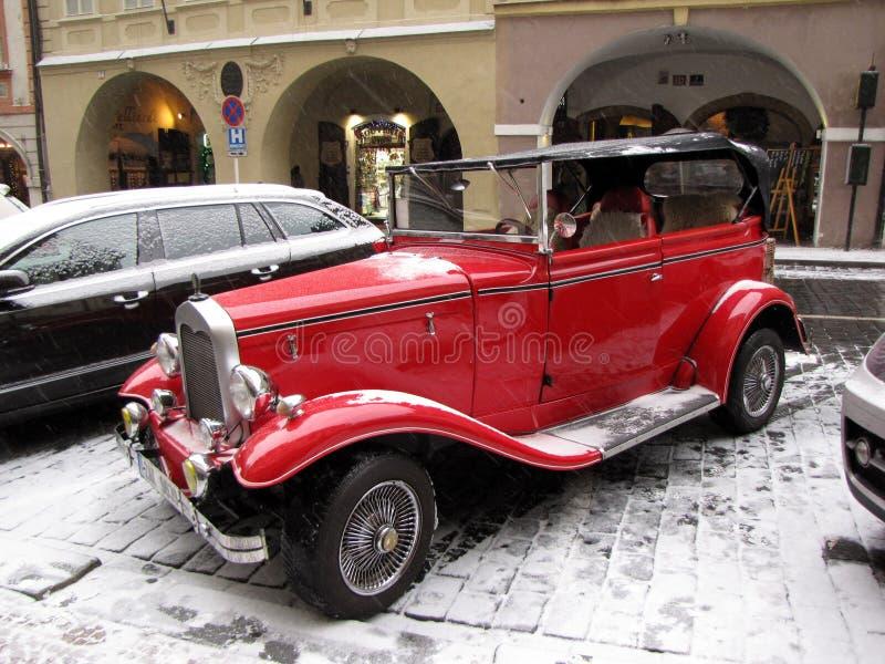 Una retro automobile di colore rosso sulle vie innevate di Praga Posto turistico nel centro di Europa Capitale medievale nella vi immagini stock libere da diritti