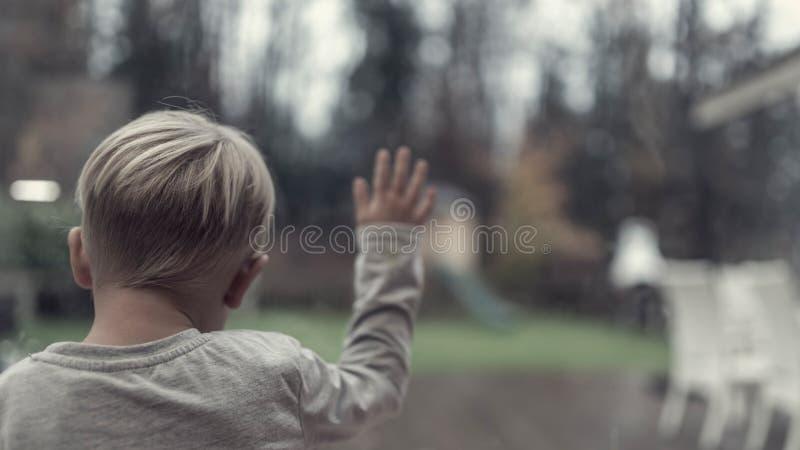 Una retro immagine di un bambino piccolo davanti ad una finestra fotografia stock libera da diritti
