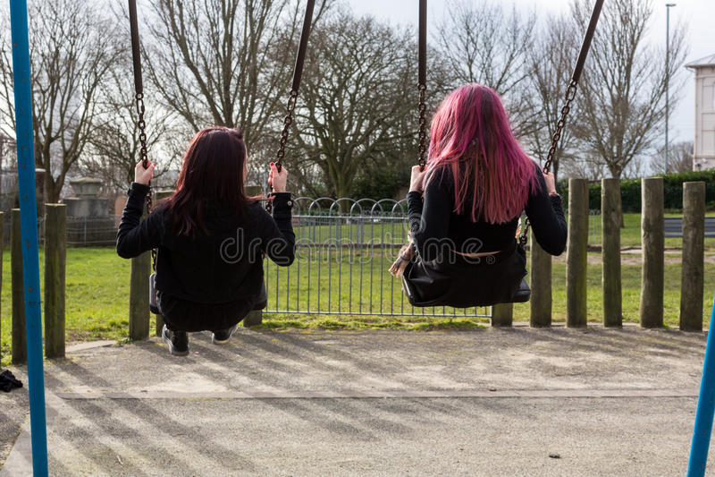 Una retrovisione di due adolescenti che oscillano sulle oscillazioni fotografia stock