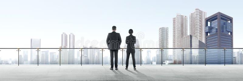 Una retrovisione di due genti di affari asiatiche che stanno sul terrazzo moderno e che esaminano vista fotografia stock libera da diritti