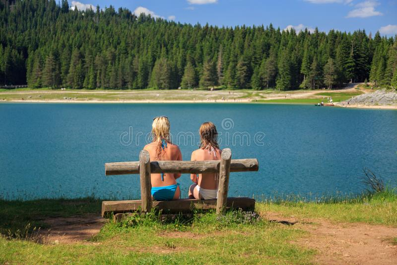 Una retrovisione di due ragazze che si siedono su un banco vicino al lago nelle montagne fotografia stock libera da diritti