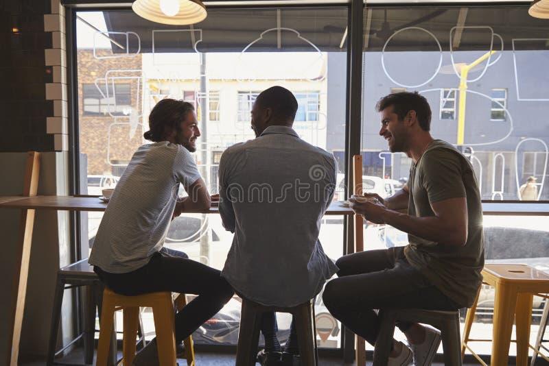 Una retrovisione di tre amici maschii che si incontrano nella caffetteria immagini stock libere da diritti