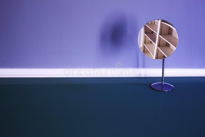 Una riflessione degli scaffali vuoti su uno specchio sopra una tavola fotografia stock