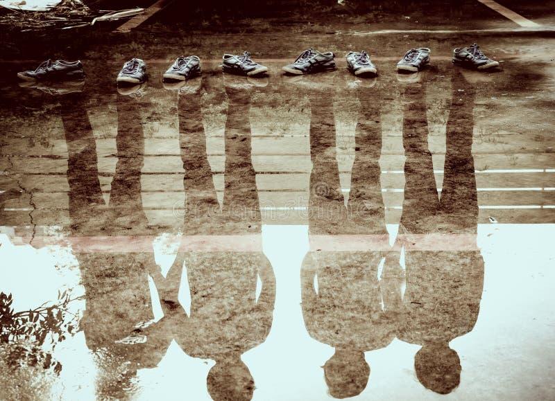 Una riflessione di quattro uomini nell'acqua dopo la pioggia, esposizione doppia fotografie stock