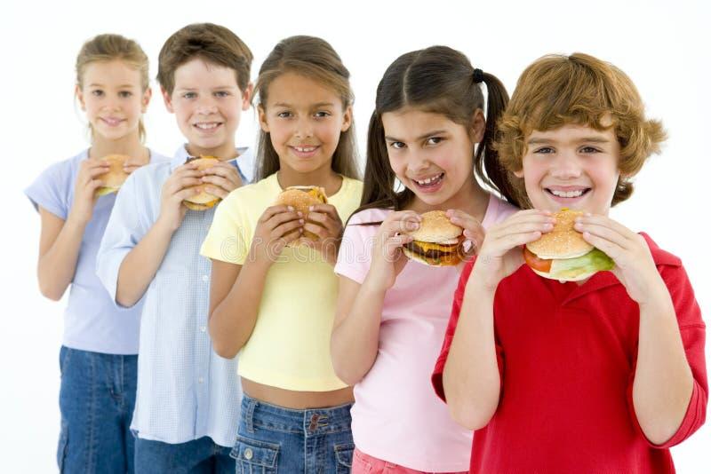 Una riga di cinque giovani amici che mangiano gli hamburger fotografia stock
