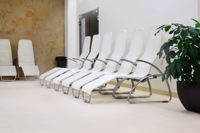 Una riga di sei sedi nella stanza vuota immagine stock libera da diritti