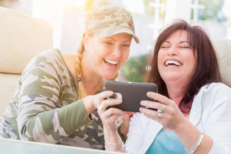 Una risata femminile di due amici mentre per mezzo di uno Smart Phone immagini stock libere da diritti