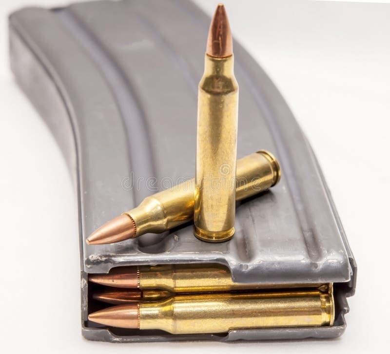 Una rivista del fucile di calibro del metallo 223 caricata con 223 pallottole di calibro con due pallottole sopra  fotografie stock libere da diritti