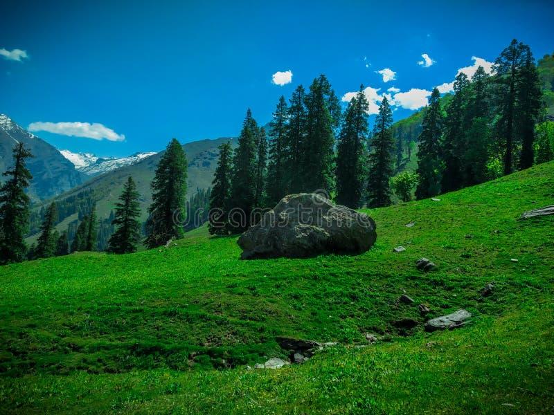 Una roca aislada en la colina con el cielo y las nubes imagen de archivo