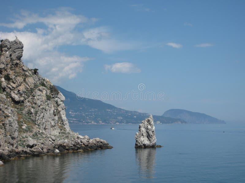 Una roccia tagliente sulla spiaggia contro un cielo blu fotografia stock