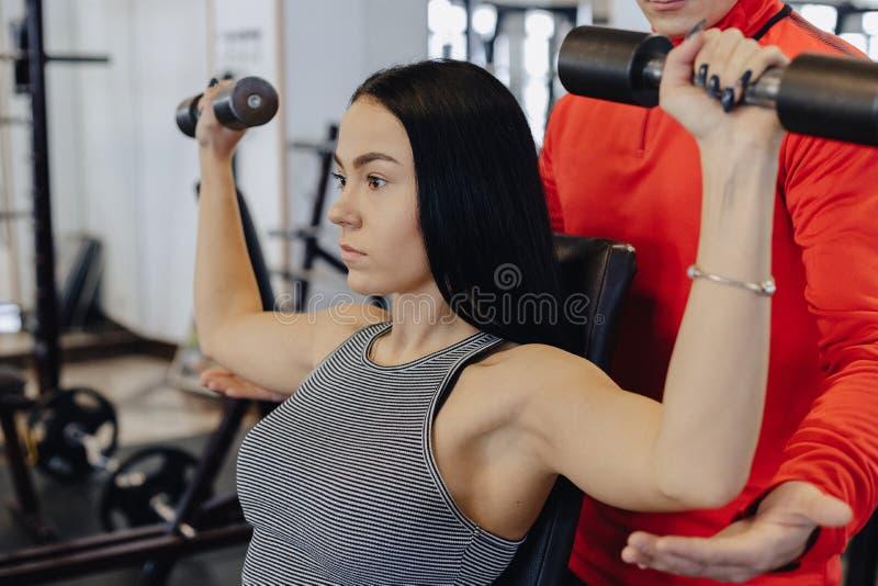 Una ropa de deportes que lleva de la chica joven en un gimnasio realiza ejercicios de la pesa de gimnasia, el coche le ayuda imagen de archivo libre de regalías