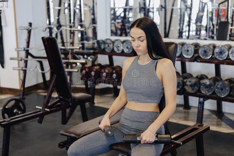 Una ropa de deportes que lleva de la chica joven en un gimnasio realiza ejercicios de la pesa de gimnasia, el coche le ayuda foto de archivo libre de regalías