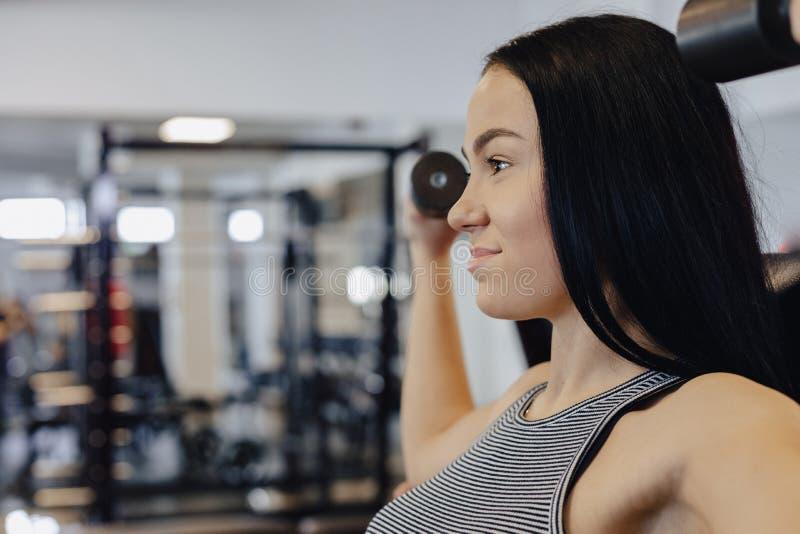 Una ropa de deportes que lleva de la chica joven en un gimnasio realiza ejercicios de la pesa de gimnasia, el coche le ayuda fotografía de archivo