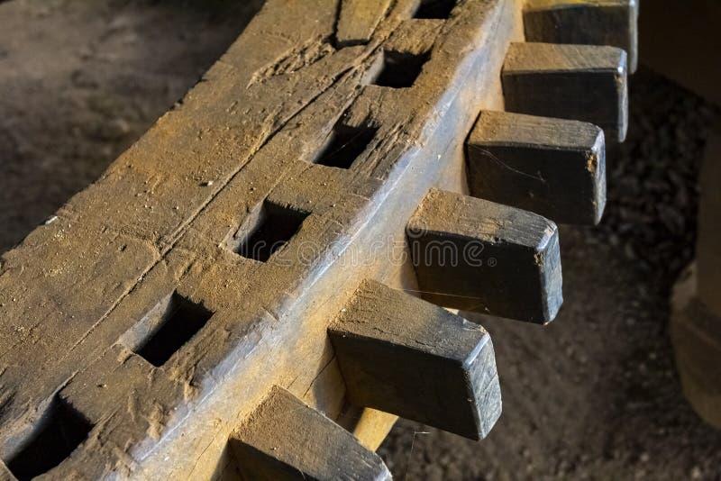 Una rueda de engranaje giratoria de madera antigua en el molino imagenes de archivo