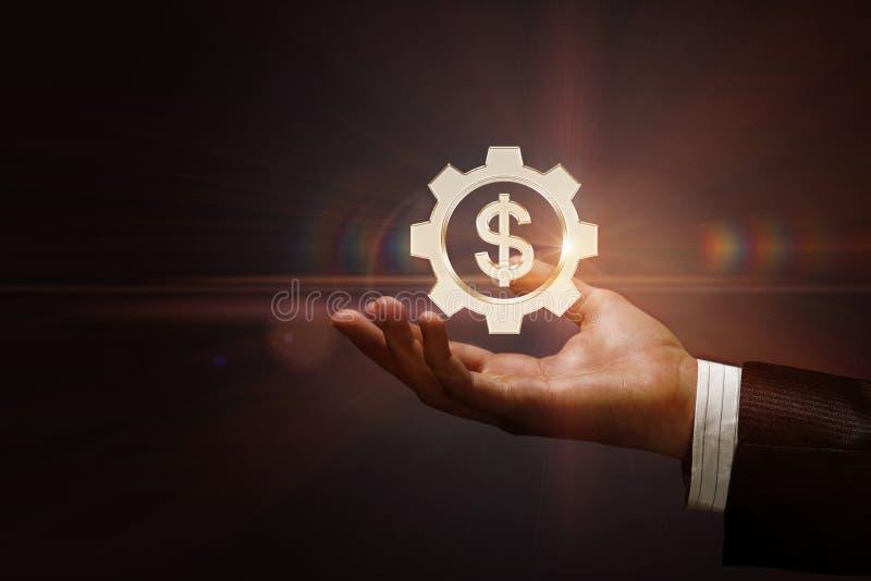 Una rueda dentada con la unidad monetaria del dólar dentro del colgante sobre la mano masculina libre illustration