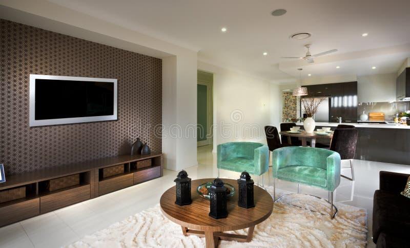 Una sala de estar cambiante decente hermosa con una TV y un kitc atado fotos de archivo libres de regalías