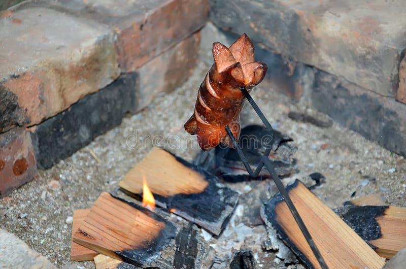 Una salchicha de asado a la parilla sobre un fuego en verano fotografía de archivo libre de regalías