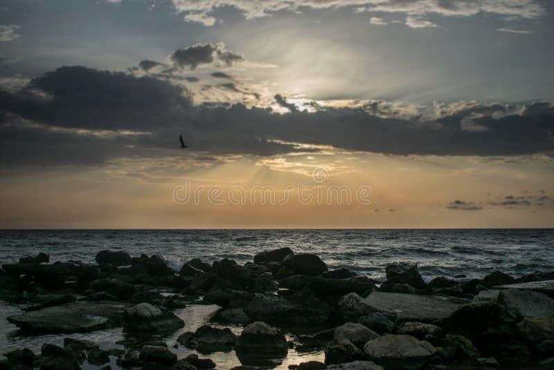 Una salida del sol hermosa en el oc?ano Barco y rocas cerca de la orilla un amanecer dramático imagenes de archivo