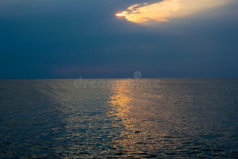 Una salida del sol hermosa en el oc?ano un cielo dramático, la tormenta se está acercando foto de archivo