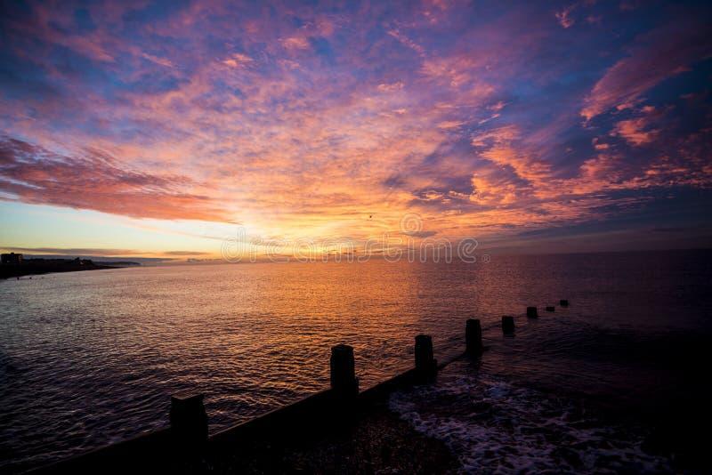 Una salida del sol imponente sobre los rompeolas de madera en la playa de Bexhill en Sussex del este, Inglaterra foto de archivo libre de regalías