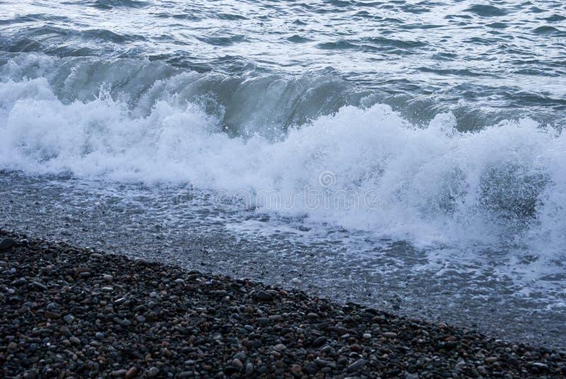 Una salida urbana de la playa de la tabla que entra en una precipitación excesiva del dren de la tormenta fotografía de archivo