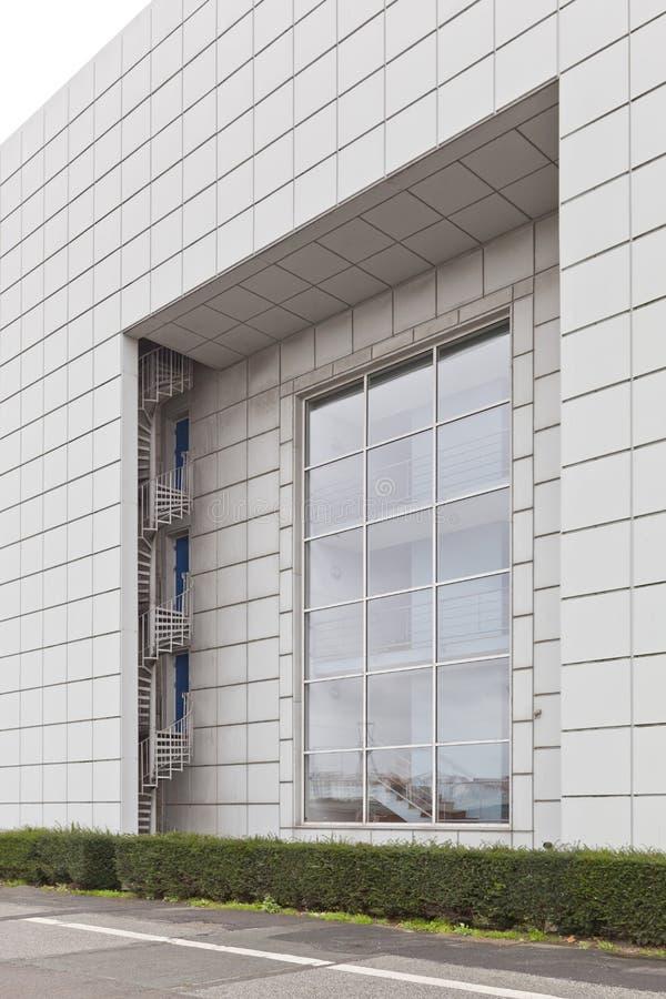 Una scala a chiocciola e una finestra enorme sulla facciata delle costruzioni moderne immagini stock libere da diritti