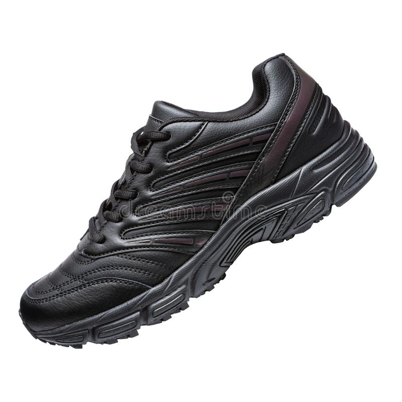 Una scarpa da tennis nera, su un fondo bianco, scarpe di sport ha inclinato fotografia stock libera da diritti