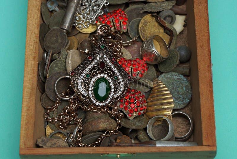 Una scatola di legno aperta con i vecchi gioielli su un fondo verde immagine stock