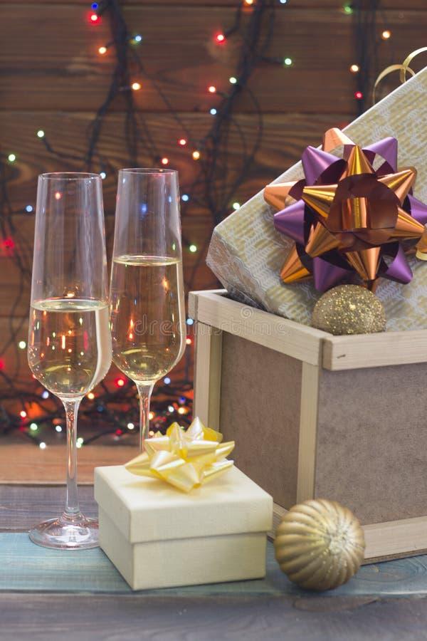 Una scatola di legno con gli ornamenti e due vetri di champagne immagine stock