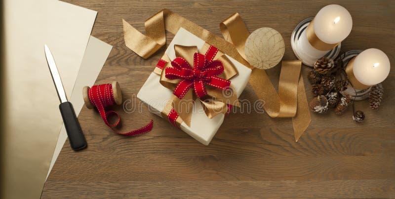 Una scatola regalo di Natale legata a prua rossa e dorata su un tavolo di legno con candele immagine stock