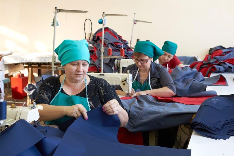 Una scena alla fabbrica per il cucito dei vestiti da lavoro Lavoro sopra fotografie stock libere da diritti