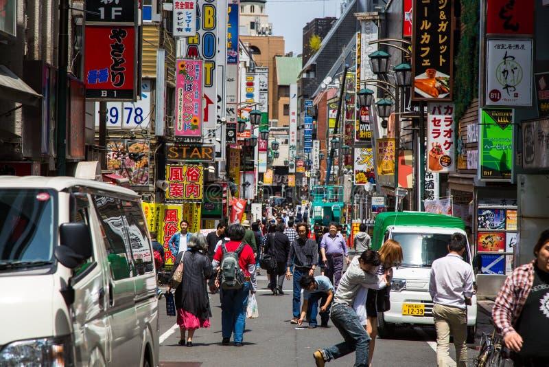 Una scena ammucchiata della via posteriore di Tokyo che mostra compera senza fine della gente e dei tabelloni per le affissioni immagine stock