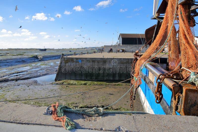 Una sciabica da pesca variopinta attraccata alla banchina con la spiaggia fangosa a bassa marea nei precedenti, Leigh sul mare fotografie stock libere da diritti